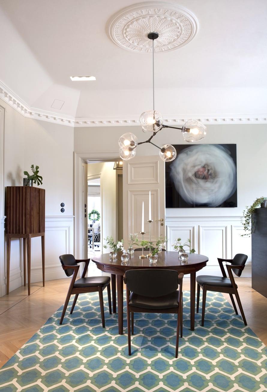 Asunnon suuresta  salongista sisustusarkkitehti Olle Rex suunnitteli keittiön ja ruokailutilan. 1950-luvun pöytä ja tuolit ovat tanskalaisen  Kai Kristensenin suunnittelemat ja kattovalaisin amerikkalaisen Lindsey Adelmanin käsialaa. Sinivihreäkuvioinen matto on Rug Companystä.