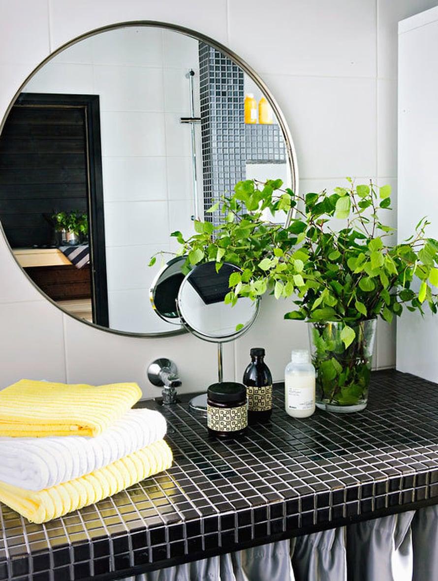 <p><p>Märkätiloissa alakaappien ovet voi korvata verhoilla. Tiloissa, joissa pinnat ovat usein kovia, tekstiilit pehmentävät ja parantavat akustiikkaa. Taso on laatoitettu Kaakelikeskuksen mattamustilla mosaiikeilla. Pyöreä peili on Ikeasta.</p></p>