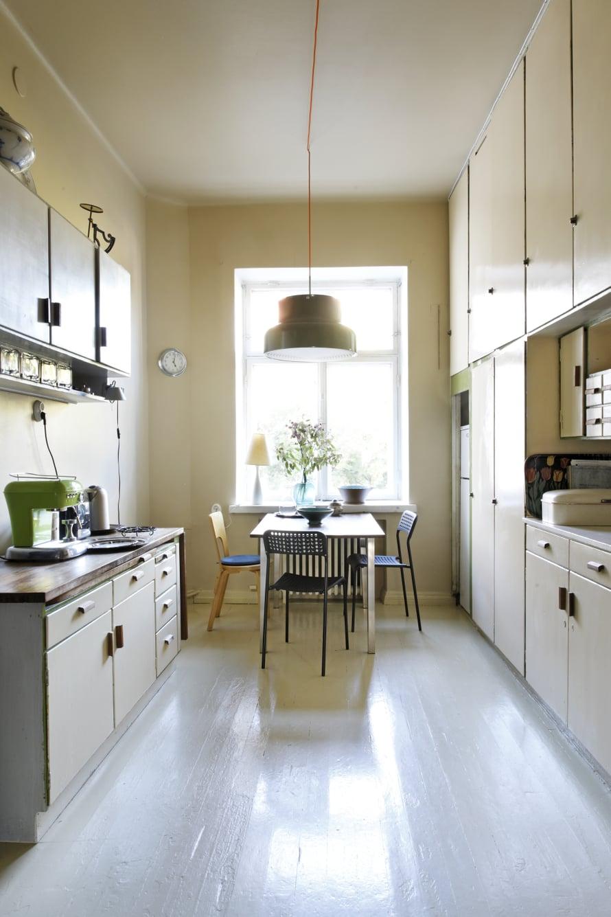Keittiö on yhä alkuperäisessä asussaan. Seinät, katto ja lattia maalattiin kaikki samalla kellertävällä sävyllä kuin kaapit, jotta tunnelmasta tuli harmoninen ja mittasuhteet hämärtyvät. Ainoat uudet hankinnat asuntoon ovat Ateljé Lyktanin Bumling-riippuvalaisin sekä Ikean mustat pikkutuolit.