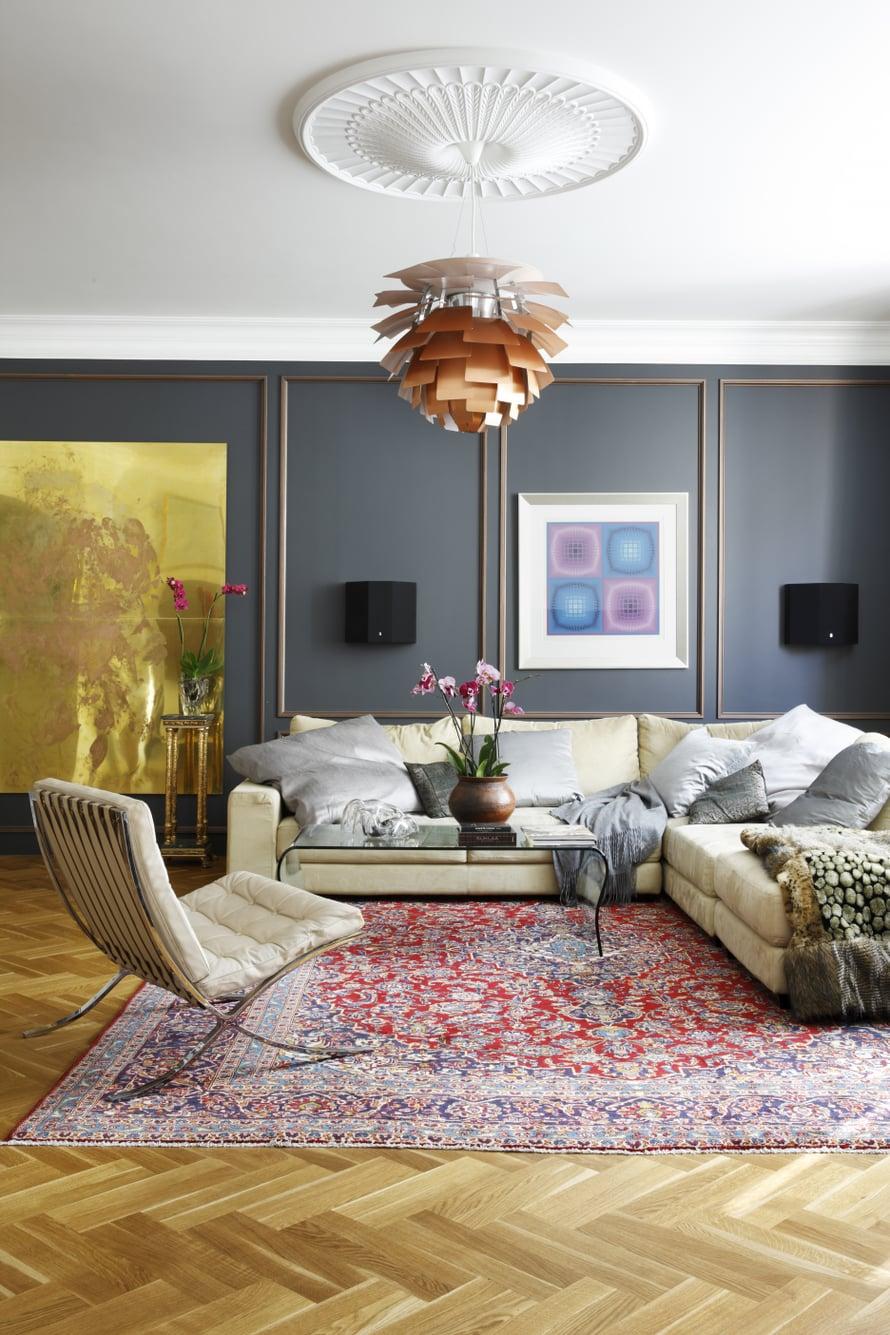 Olohuoneen seinät paneloitiin tummilla puupaneeleilla, joihin maalattiin pronssin-sävyiset koristelistat. Punasävyinen Keshan-matto ja Barcelona-tuoli ovat huutokauppalöytöjä. Lasipöytä on hankittu Vepsäläiseltä. Sohvan päällä on Victor Vasarelyn työ.