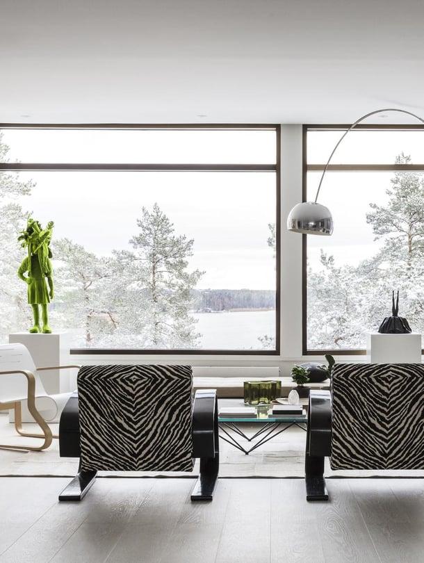 Olohuoneen rauhallinen sisustus antaa tilaa luonnolle ja taiteelle. Sohvan päällä on Susanne Gottbergin työ. Värikäs Doggy Style -teos on Riiko Sakkisen tilaustyö. Sammaltyttö on Kim Simonssonin käsialaa, Charlotte Gyllenhammarin patsas on hankittu Ruotsista. Kermanvaalea sohva HT-Collection, tuolit Artek, sohvapöytä B&B Italia ja lattiavalaisin Flosin Arco.