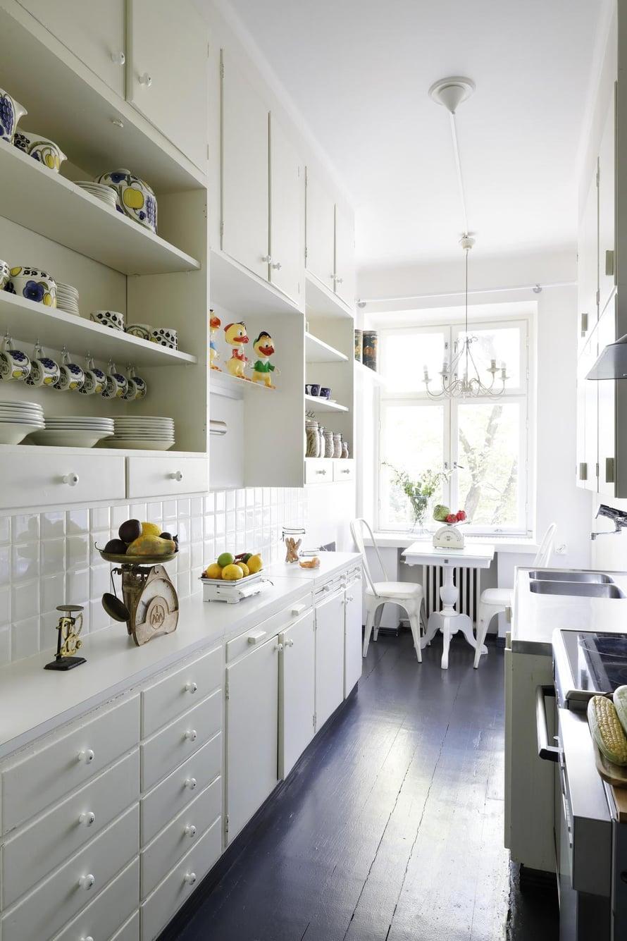 Keittiössä on alkuperäiset kaapistot, joista Ella ei halunnut luopua ergonomiankaan nimissä. Samassa talossa asui aikanaan  astiankuivaus-kaapin keksijä Maiju Gebhard, jonka ansiosta asuntoihin asennettiin tuo aikoinaan ultramoderni keksintö. Keittiön metalliset tuolit ovat Plootusta, pöytä on Rivièra Maisonin.