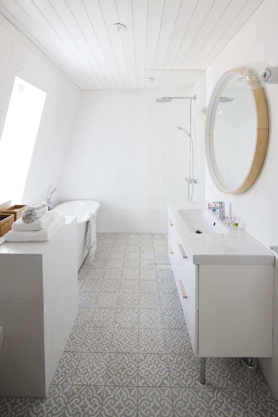Yläkerran ikkunallisessa kylpyhuoneessa on lempeä väriskaala. Vino ikkuna ja sen viereen sijoitettu kylpyamme ovat arjen ylellisyyttä. Laatoitettu taso erottaa wc:n ja kylpytilan toisistaan ja kätkee sisälleen pyykkikuilun suoraan kodinhoitohuoneeseen.