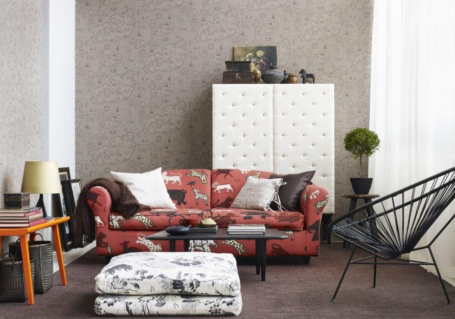 Persoonalliset kuosit yhdistävät olohuoneen tyylin hauskaksi kokonaisuudeksi. Ruosteenpunainen, viidakoneläimillä koristeltu sohva on huoneen väripilkku. Seinällä on aarrekarttaa muistuttava Sandbergin Ferdinand Ljustbeige -tapetti. Kuva: Sandberg