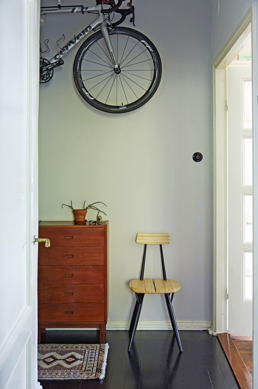 Menopeli seinällä säästää tilaa. Lipasto on hankittu Antiikkiliike Fasaanista. Pirkka-tuolille on kätevä laskea laukku kotiin tultaessa.