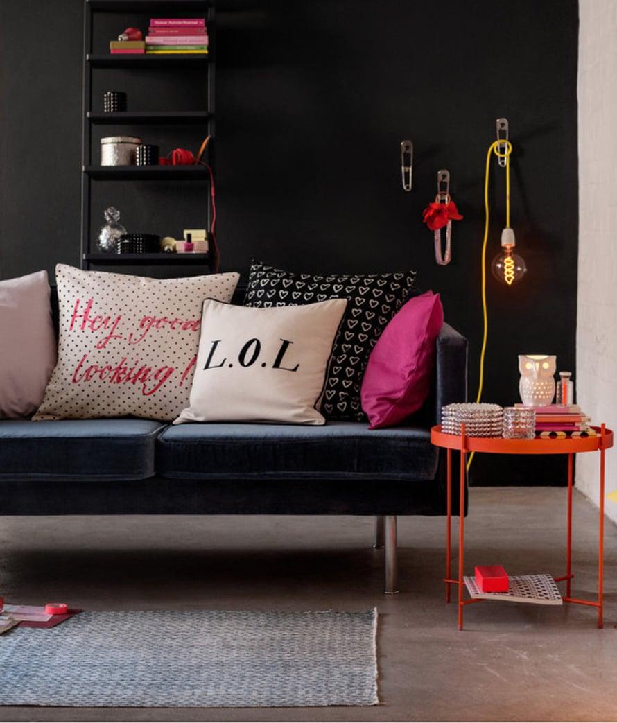 """Musta sein&auml; ja musta sohva saavat loistavasti yhteen sopivat oranssin, keltaisen ja punaisen eri s&auml;vyt pompahtamaan esiin sisustuksessa. Pilkullinen tyynynp&auml;&auml;llinen tekstill&auml; 7,99 e. Kuva: <a href=""""http://www.hm.com/fi"""" target=""""_blank"""">H&amp;M</a>"""