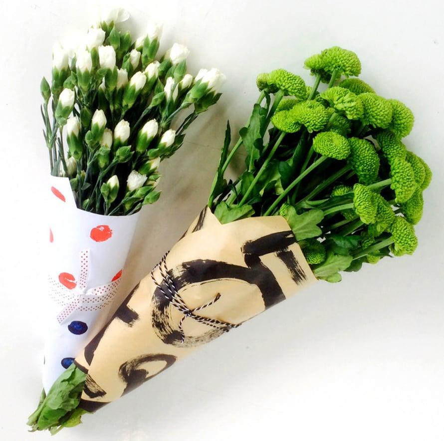 Porkkanaleimattu paperi sai sisäänsä neilikoita ja ympärilleen pilkullista nauhaa, graafisilla kuvioilla koristeltu voimapaperi täydentyi mustavalkoisella pakkauslangalla ja raikkailla vihreillä krysanteemeillä.