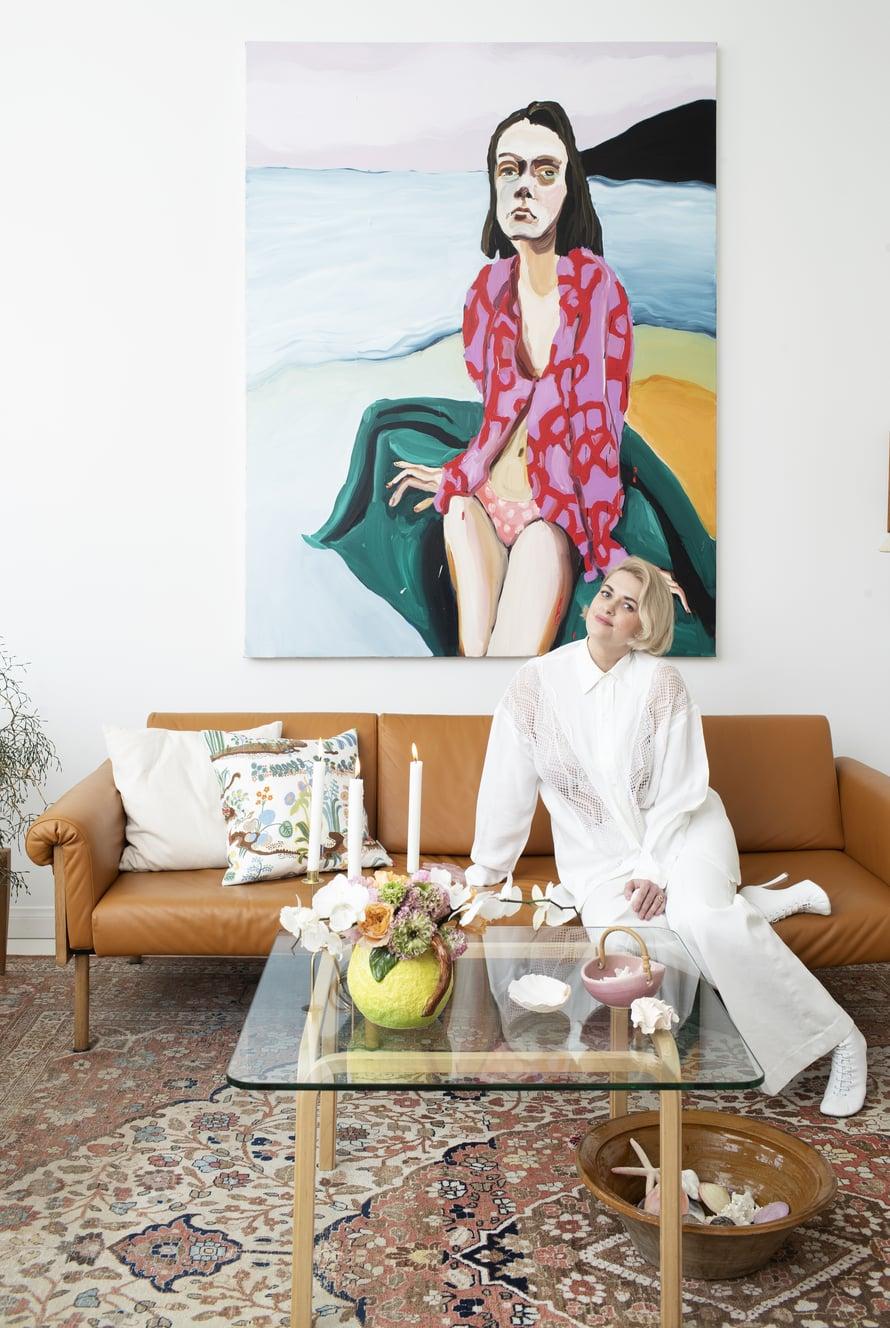 """Jenni Hiltusen Sunset kuljettaa lomatunnelmaan. Jennin taulut olivat Sannin pitkäaikainen haave. """"Rakastan katselevia naisia kotini seinillä. Niiden ympärille rakennan loppuelämäni kodin."""" Artekin pöytä on Fasaani-antiikki-liikkeestä."""