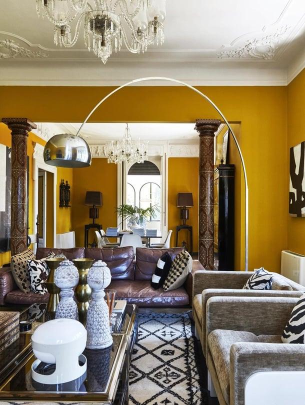 Olohuoneessa Malenen valitsema yllätysväri keltainen tuo upeasti esiin huonekalut ja taiteen. Pitkä sivupöytä on Malenen omasta kotimallistosta vuodelta 2014 ja valaisimet vuoden 2018 kokoelmasta.