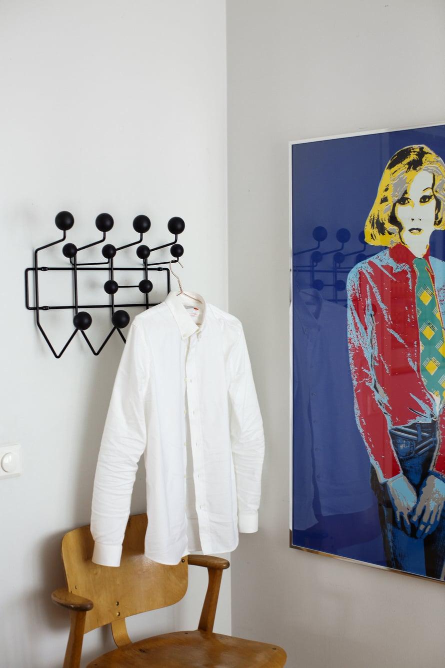 Ilmari Tapiovaaran Domus-tuoli pitää makuuhuoneessa seuraa Charles ja Ray Eamesin Vitralle suunnittelemalle Hang it all -naulakolle. Taulu on Kari Riipisen.