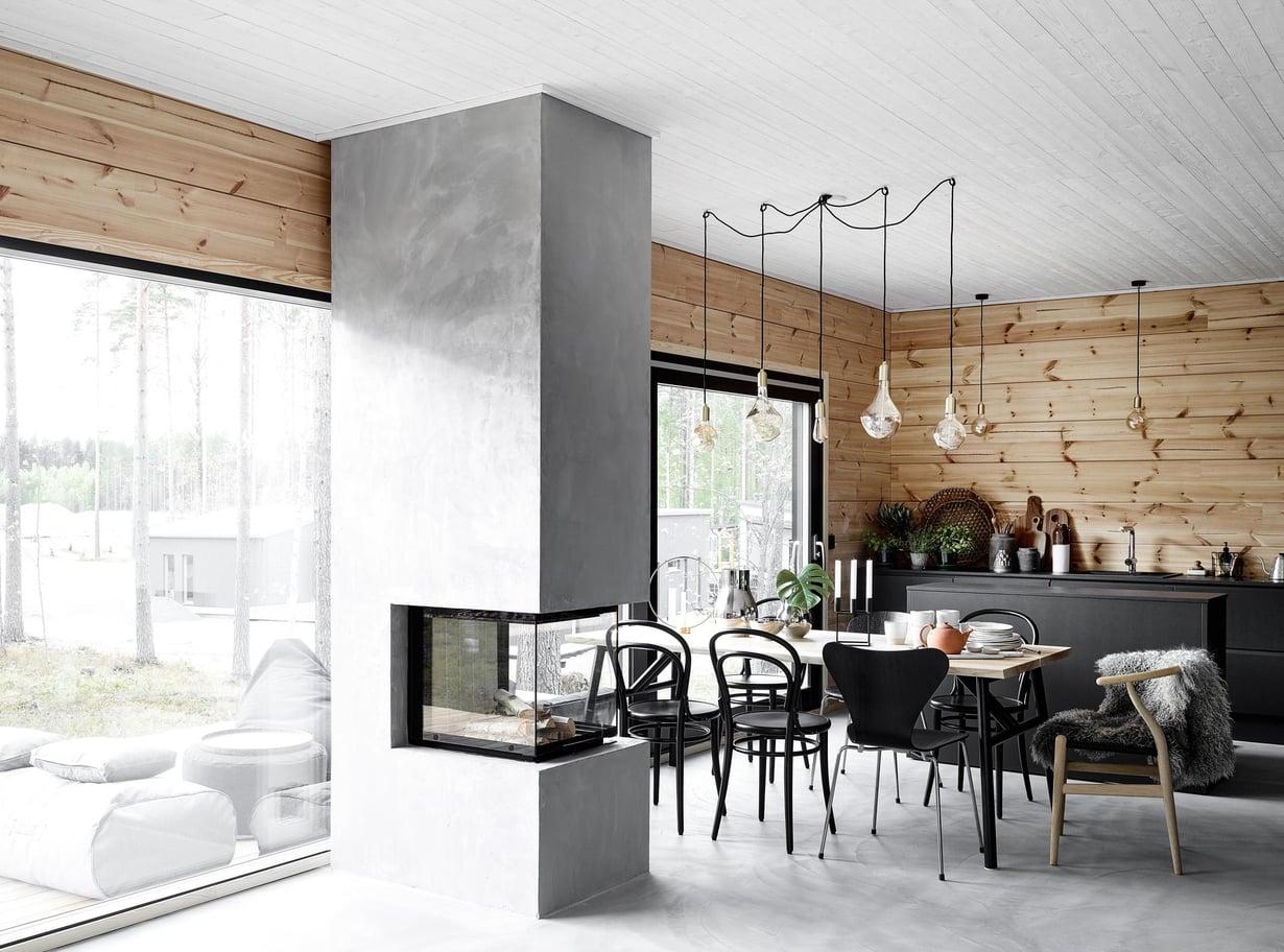 Alakerta on yhtä suurta tilaa, jonka jakaa mikrobetonilla pinnoitettu takka. Keittiö on Nixi-keittiöiden mallistosta, ja Dekton Domoos-taso on Edelstein Specialista. Keittiön toinen seinusta on yläkaapiton, jotta kaunis hirsiseinä näkyy. Ruokapöytä on Hakolan, Tonin tuolit ovat Formesta. Fritz Hansenin Seiska-tuolit ja CH24-tuoli ovat Nomartista, lampaantalja Tiirinkosken Tehtaasta. Koristeelliset lamput ovat Talan Voronoi I ja II.