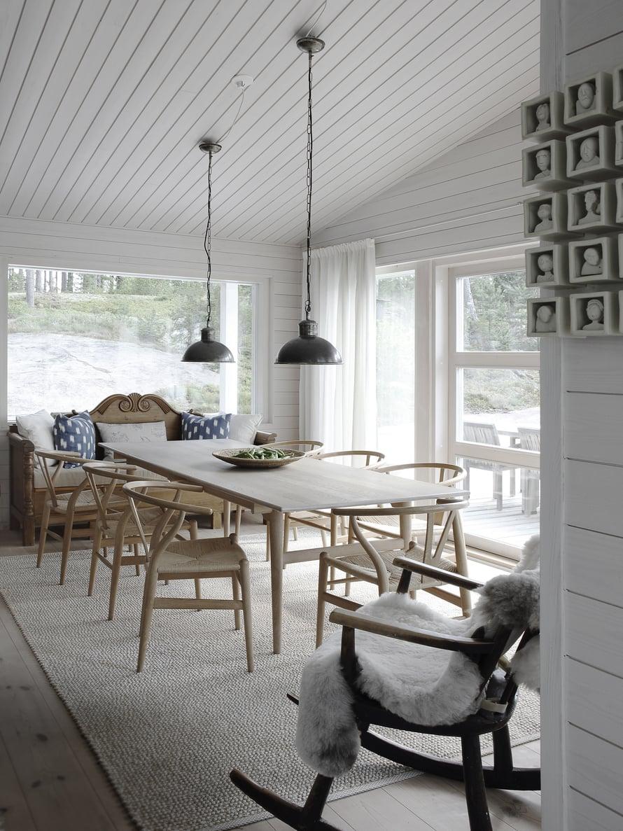 Ruokailutila on aivan keittiön kyljessä. Sisustuksen helmet ovat Hans J. Wegnerin ruokapöytä ja CH24-tuolit. Niiden kevyt rakenne ja kaunis muotoilu sopivat yhteen Matin perintökeinutuolin ja Fiskarsin antiikkimarkkinoilta ostetun talonpoikaissohvan kanssa.