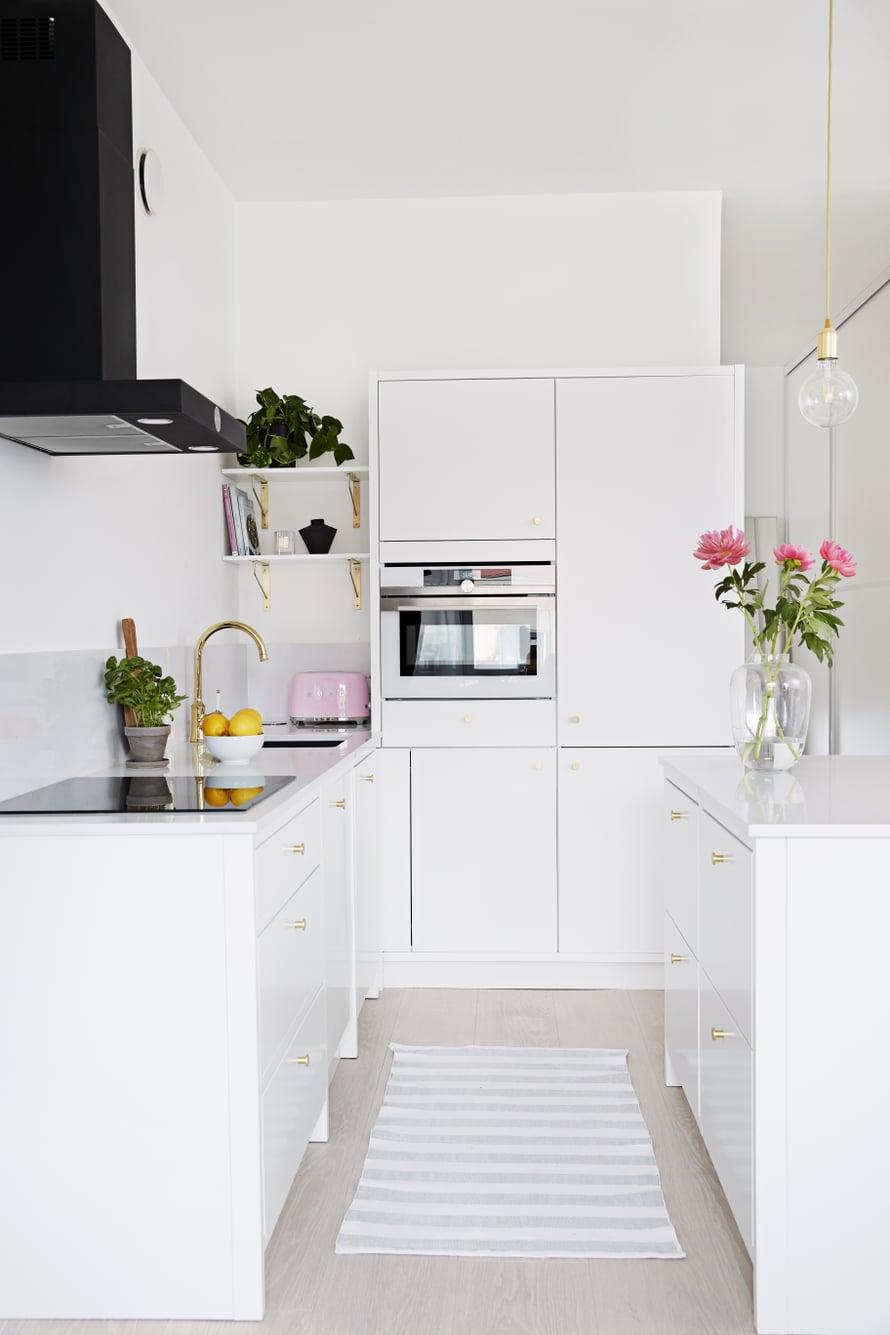Janna valitsi keittiöönsä runsaasti messinkisiä yksityiskohtia sekä mustan liesituulettimen tuomaan ryhtiä muuten vaaleaan kokonaisuuteen.