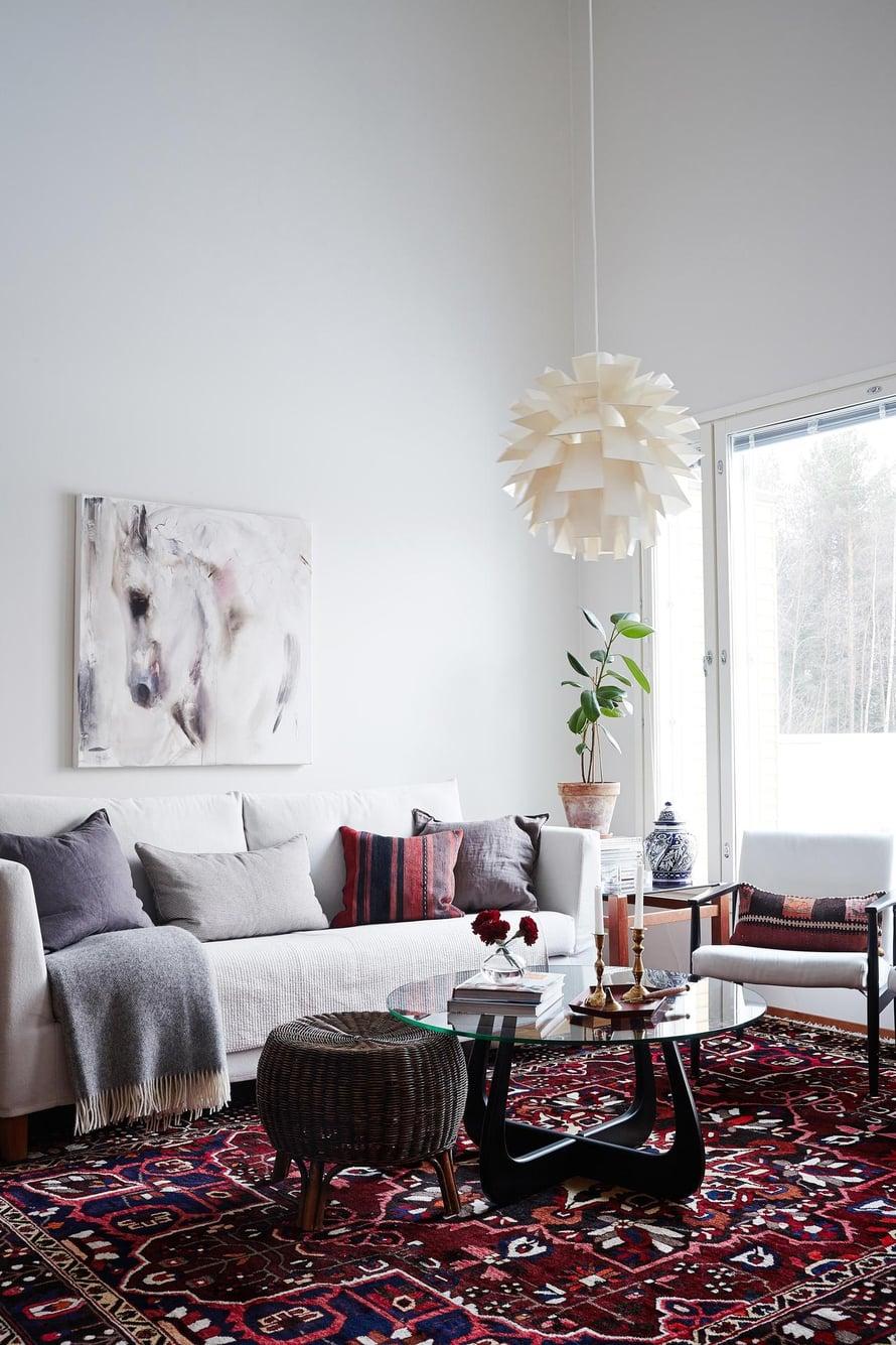 Olohuoneen matto  on Carpetvistasta ja Elinan mielestä täydellinen tyydyttämään värinhimoa. HT-Collectionin sohvan ja sohvapöydän Elina  hankki nettihuutokaupasta. Sohvan yllä  on Katja Hannulan Heijastuksia-teos.