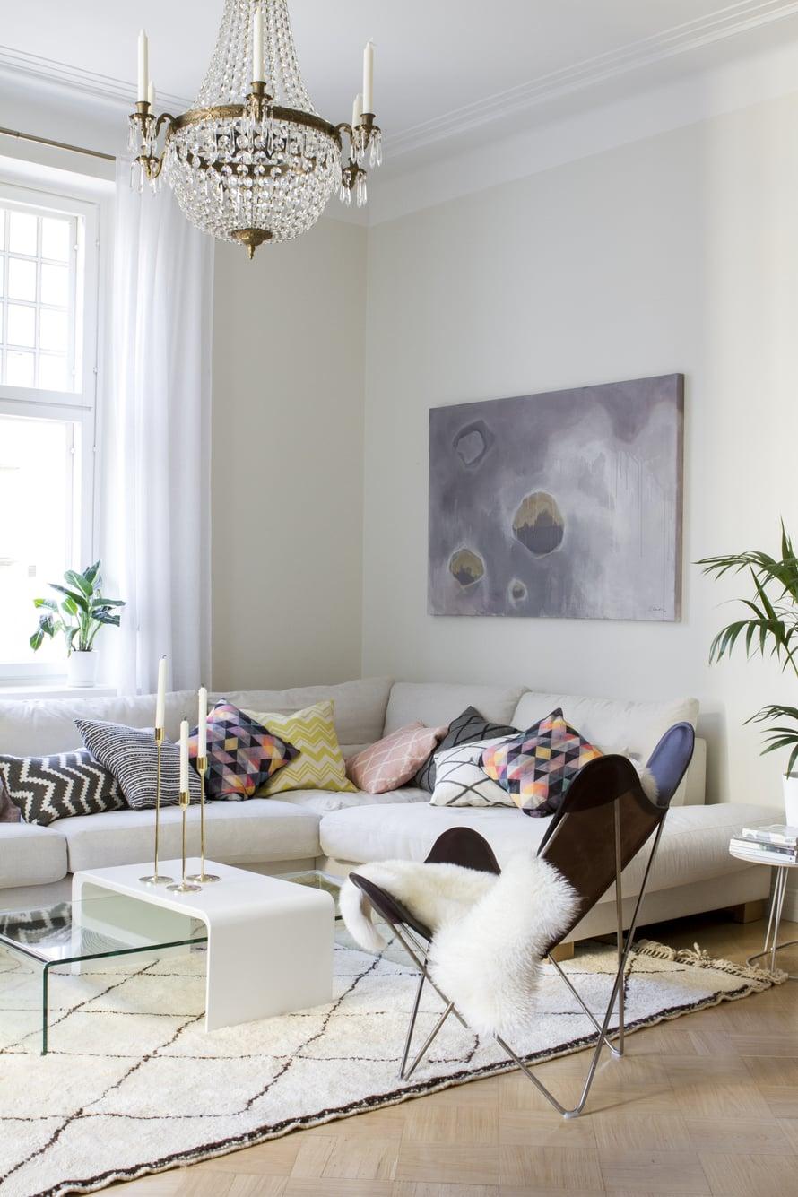 Asukkaat halusivat säilyttää remontissa niin paljon alkuperäistä kuin mahdollista. Olohuoneessa on alkuperäinen Billnäsin ruutuparketti, joka valkokuultolakattiin. Seinät on maalattu Tikkurilan Briesävyllä. Seinällä on asunnon pintaremontista vastanneen suunnittelijan Sebastian Sandelinin maalaus Golden Sunset. Lepakkotuoli, messinkiset Nattlight-kynttilänjalat ja ikat-kuvioiset tyynyt ovat Zarrosta.