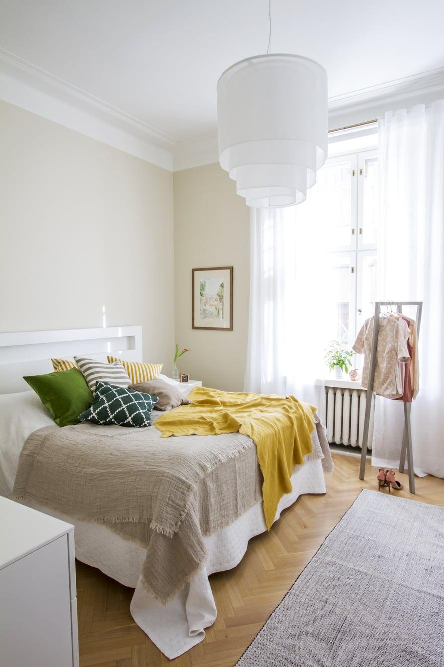 Makuuhuoneen värimaailma on poimittu seinälle ripustetusta akvarellista. Seinät maalattiin himmeällä Tikkurilan Symphonyn Tofu-sävyllä. Hiekan värinen pellavainen päiväpeitto, keltainen shaali, samettityynyt ja ikat-kuvioinen tyyny ovat Mokosta, Hayn vaateteline henkareineen on Formverkista sekä vaatteet ja matto Dotsista.