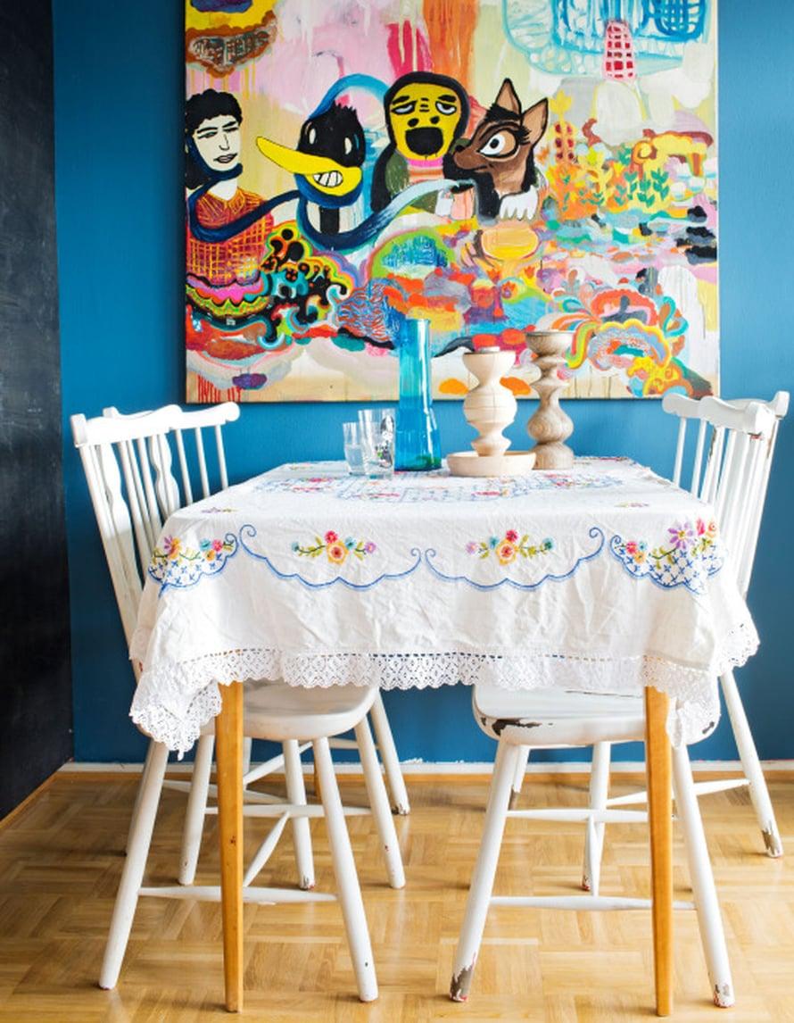 """""""Mietin olohuoneen sinistä väriä vuoden verran ennen kuin tein päätöksen seinän maalaamisesta. Rakastan kirjailtuja pöytäliinoja. Niillä on helppo muuttaa ruokailutilan tunnelma arkisesta romanttiseksi"""", Meri-Tuuli kertoo. Maalaus on Ville-Veikko Viikilän."""