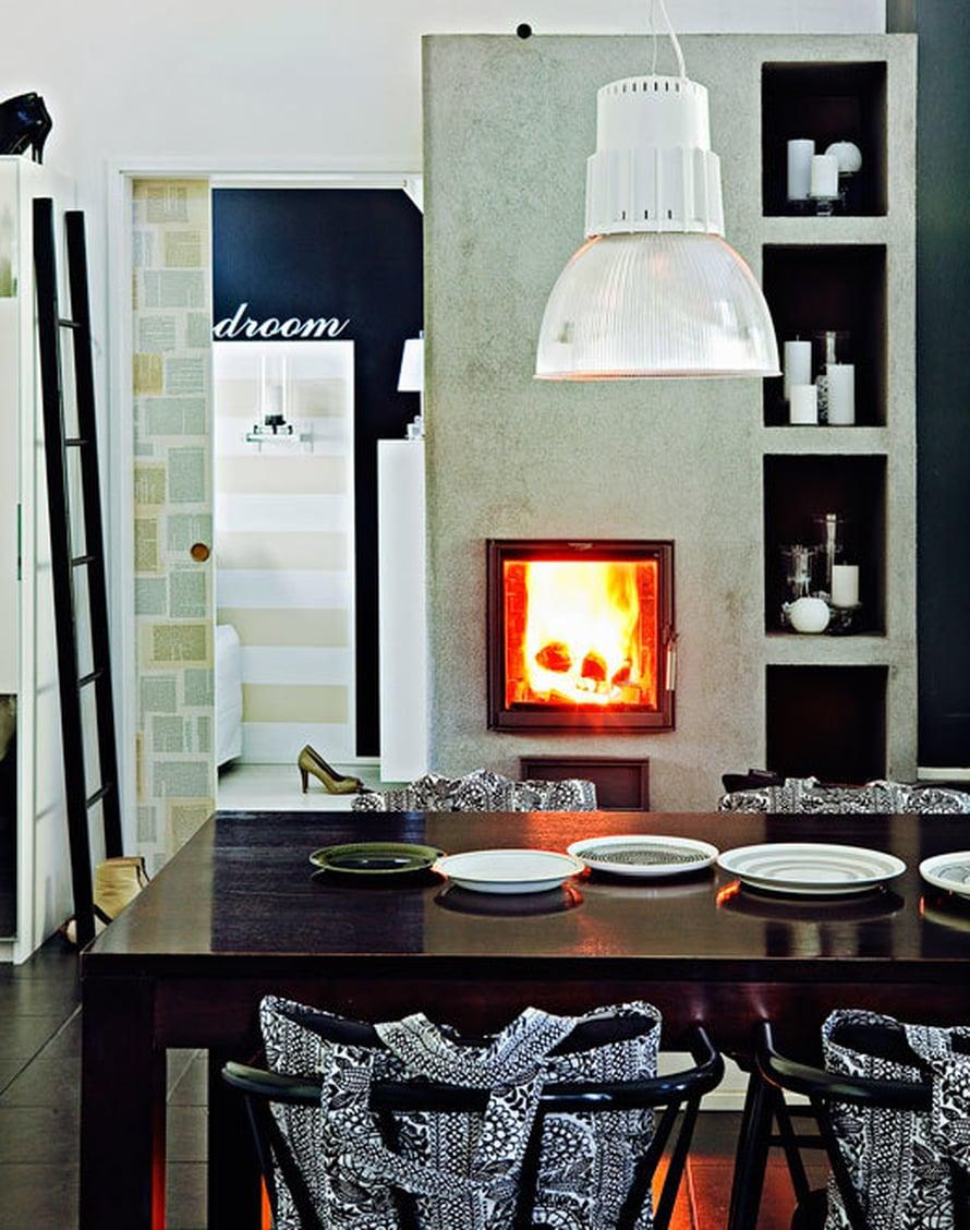 <p><p>Tulikiven Viola-takka on keskeisellä paikalla, ja tuli näkyy kauniisti keittiöön, ruokailutilaan ja olohuoneeseen. Maalattuaan kierrätyskeskuksen pinnatuolit mustaksi Minna pehmusti selkänojat tyynyillä täytetyillä Finlaysonin kasseilla. Ruokapöydän päällä olevat valaisimet ovat Livalin. </p></p>