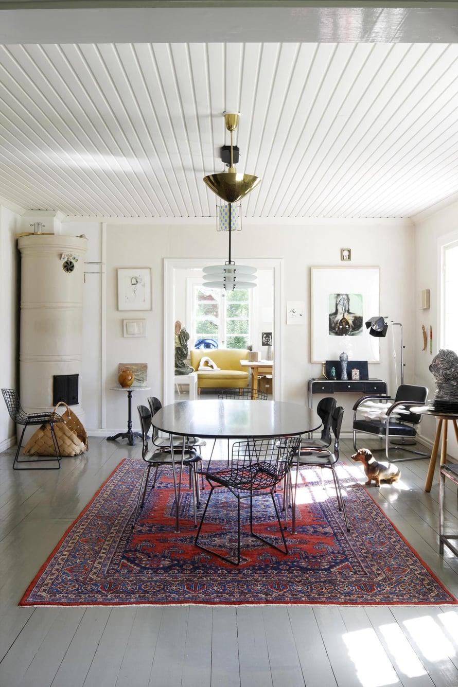Ruokailuhuone on keskellä alakertaa, ja sieltä on näkymät työhuoneeseen ja olohuoneeseen. Koska talon isännällä on useita kattovalaisimia, hän sijoitti kolme niistä Fritz Hansenin ruokapöydän päälle. Pöydän ympärillä on Arne Jacobsenin Muurahaistuolit ja Knollin Bertoia-tuolit. Jalkalamppu on Yrjö Kukkapuron suunnittelema.