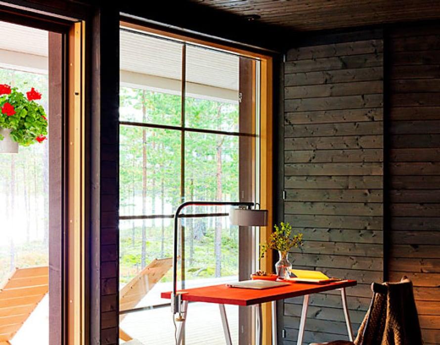 <p><p>Petri ideoi Saimille työpöydäksi siron pukkijalkapöydän. Jalat ovat Ikeasta. Saunamökin parketti maalattiin vaaleanharmaaksi. 30 neliön rakennuksen lattiasta kattoon ulottuvista ikkunoista näkyy tyyni Puruvesi. </p></p>